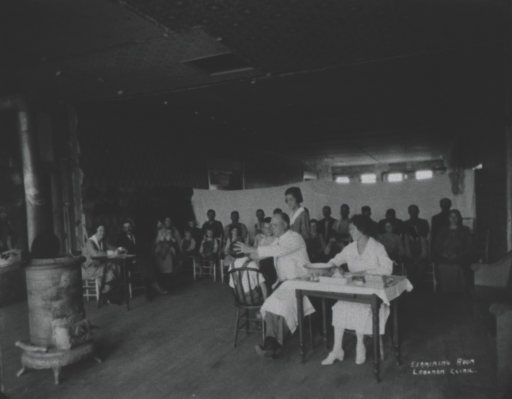 <p>Interior view of a temporary trachoma clinic; curtins hang in the background dividing the room; patients are sitting in front of the curtins observing the physician in the foreground as he treats a young child; cast-iron stove is on the left.</p>