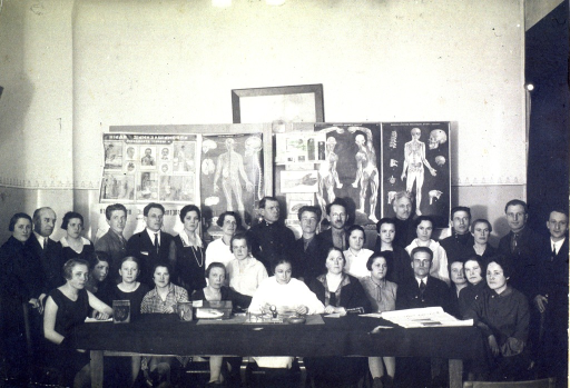 <p>A group of male and female students poses behind a long table in a classroom.  There are medical posters in Russian on the wall behind the people.</p>