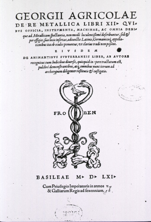 <p>The Froben printer's mark is a staff entwined with serpents and topped with a bird; the staff is held by two left hands that appear from clouds at the sides.</p>