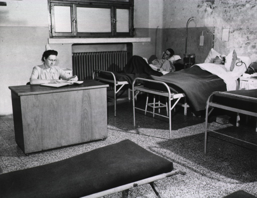 <p>A female nurse sits and reads at a desk next to a row of hospital beds in a ward.  Two male military personnel can be seen lying in beds.</p>