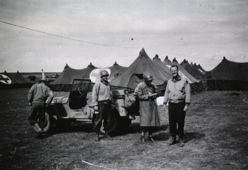 <p>Several military personnel stand next to an army jeep.  In the background are rows of tents.</p>