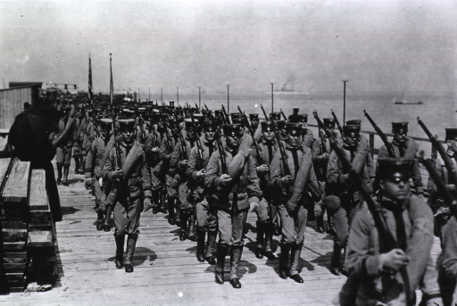 <p>View of United States uniformed soldiers carrying rifles, marching on a boardwalk along a waterfront.</p>