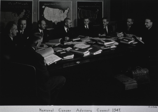 <p>Several men are seated around a large table on which are piled many reports; three maps of United States appear on the wall in the background.</p>