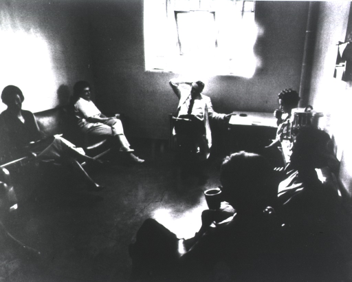 <p>A group of people, including the male physician and female patients, sits in a circle on chairs in a room lit by an open window.</p>