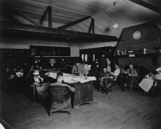 <p>Interior view: the room has a fireplace, bookshelves, a table, light fixtures hanging from the ceiling, and crutches leaning against a table; in the background there is the entryway to, and windows in, another room.  People are sitting and standing while reading.</p>