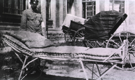<p>A member of the medical staff displays a German Red Cross Hospital bed and mattress.</p>