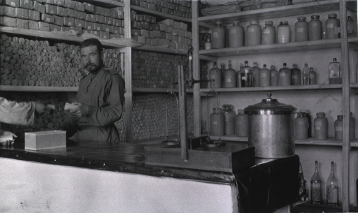 <p>One member of the medical personnel staff stands at the counter of the dispensary at Military Hospital No. 16.</p>