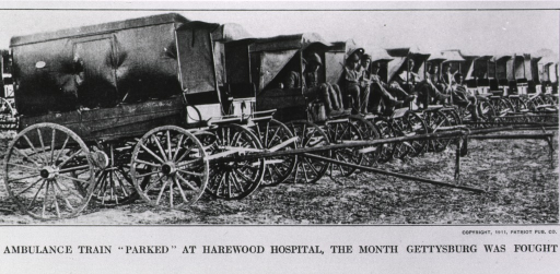 <p>A row of horse-drawn ambulances, without the horses, parked in a field; men are seated in some of the ambulances.</p>