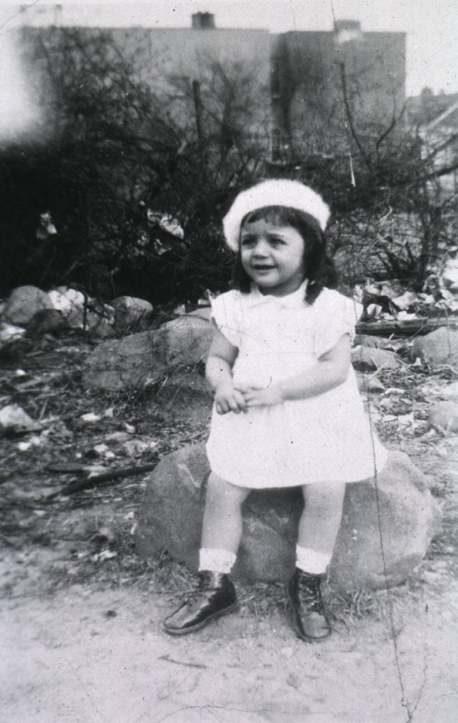 <p>Showing Teresa sitting on a rock wearing a dress and a hat.</p>