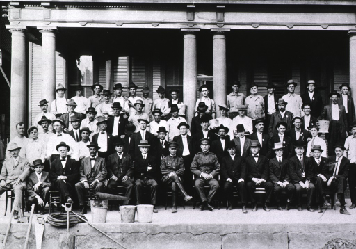 <p>Group portrait of 2 U.S. Public Health Service officers (front row, center) and sanitary workers during the New Orleans plague campaign; rat-collection buckets and other equipment used in rat eradication efforts are visible.</p>