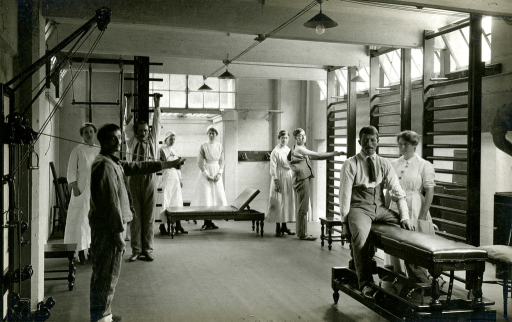 <p>Black and white photograph of the massage exercise room at King George Military Hospital, London, England. 4 patients are using equipment in the room and there are 5 nurses with them.</p>