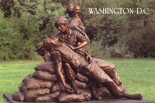 <p>Postcard featuring a color photograph of a sculpture featuring a uniformed woman sitting on sandbags and holding a wounded man on her lap. She is pressing her hand to his chest. Behind her are two other uniformed women, one standing and one sitting. Behind the monument is a background of trees.</p>