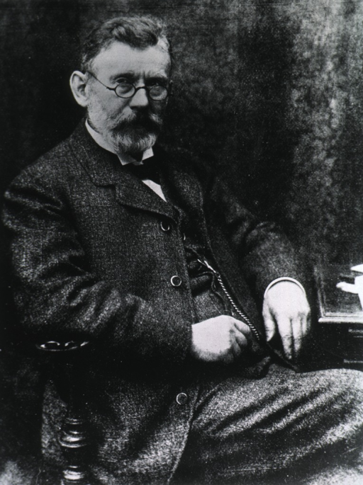 <p>Three-quarter length, seated, right pose, wearing glasses.</p>