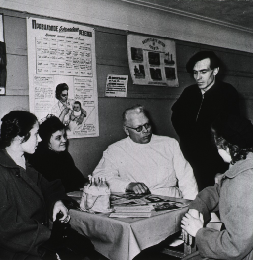 <p>A physician is seated at a table with three women; a man is standing next to the physician; on the wall behind them is a poster showing a mother feeding an infant; on the table are four bottles with cotton (?) stoppers.</p>