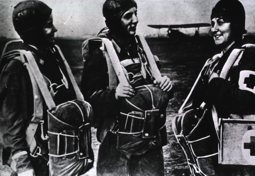 <p>Three women wearing aviation uniforms and parachutes; an airplane is in the background.</p>