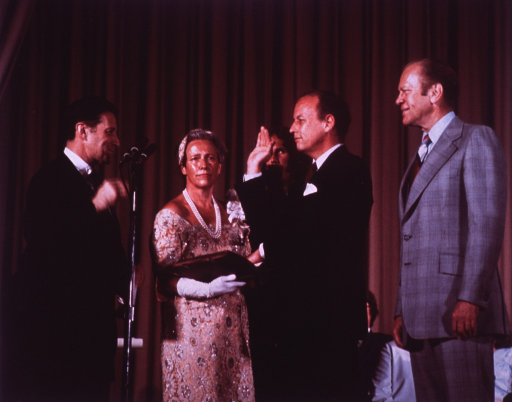 <p>At the swearing in of Donald S. Fredrickson as the 11th director of the National Institutes of Health, Caspar W. Weinberger, secretary of the Dept. of Health, Education, and Welfare, is standing next to Mrs. Henriette Fredrickson who is holding an open book.  Dr. Fredrickson is raising his right hand and his left hand is on the book.  Eric Fredrickson is to Dr. Fredrickson's right and President Gerald R. Ford is to his left.  They are in Masur Auditorium in front of a stage curtain.  People are seated in front of the curtain.</p>