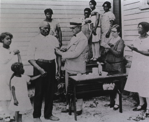 <p>A family stands in front of a building. A physician inoculates the father, while the other family members watch and prepare their own upper arms for the procedure.</p>