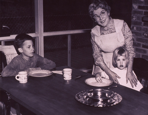 <p>Homemaker is standing with two children seated at a table set for dinner.</p>