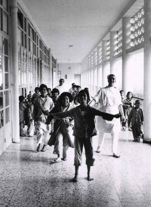 <p>Many children are walking along a corridor which has doors on one side and is open on the other.</p>