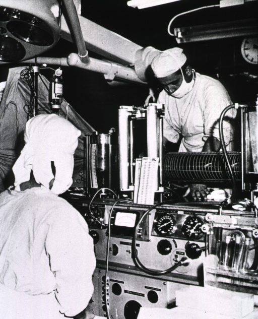 <p>Interior view of an operating room: during an operation a patient is connected to a large mechanical device that performs the functions of the heart. Technicians are monitoring the device.</p>