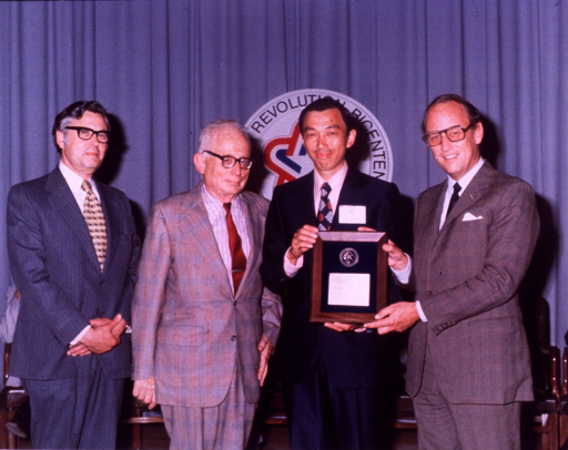 <p>Donald S. Fredrickson, director of the National Institutes of Health (NIH), is holding the Director's Award with Philip Chen, assistant to the deputy director (science).  Next to Dr. Chen is Deputy Director (science) Dewitt S. Stetten.  Dr. Ronald Lamont-Havers, deputy director of NIH, is on the far left of the picture.  They are standing in front of a stage curtain.  There are chairs behind them.</p>