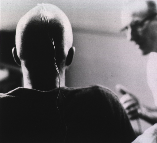 <p>Rear-view of a bald-headed man with electrodes extending from the top of his head down his back; another man faces him and holds an apparatus.</p>
