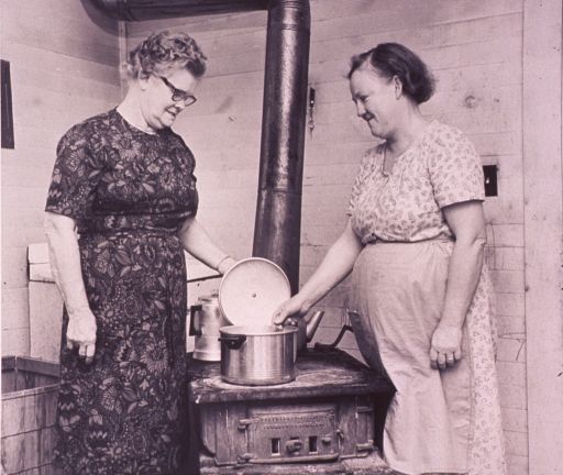 <p>Homemaker and another woman are preparing a meal on a woodburning stove.</p>