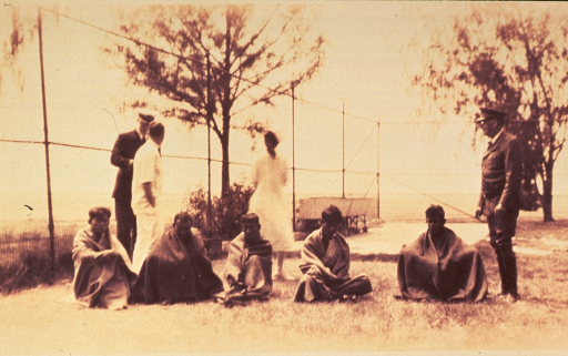 <p>Exterior view: five Filipino meningitis patients are sitting on the ground; standing nearby are physicians and a nurse.</p>