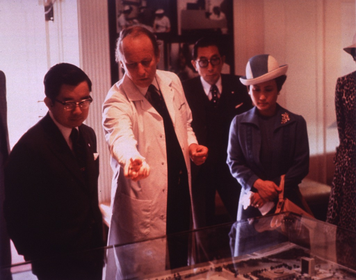 <p>Prince Masahito Hitachi and Princess Hanako Hitachi are in Building 1 of the National Institutes of Health (NIH) looking at a map with Dr. Donald S. Fredrickson, director of NIH.  There is a man standing behind them and a partial view of a woman.  Behind them is a pictorial display of nurses at a patient's bedside and a researcher with a microscope.</p>