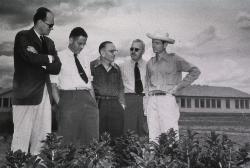 <p>A group of men stand together in a field; building in the background.</p>
