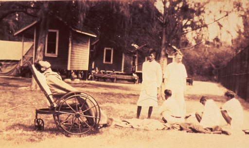 <p>Exterior view: a meningitis patient is sitting in a wheelchair; others are sitting on the ground; buildings in background.</p>