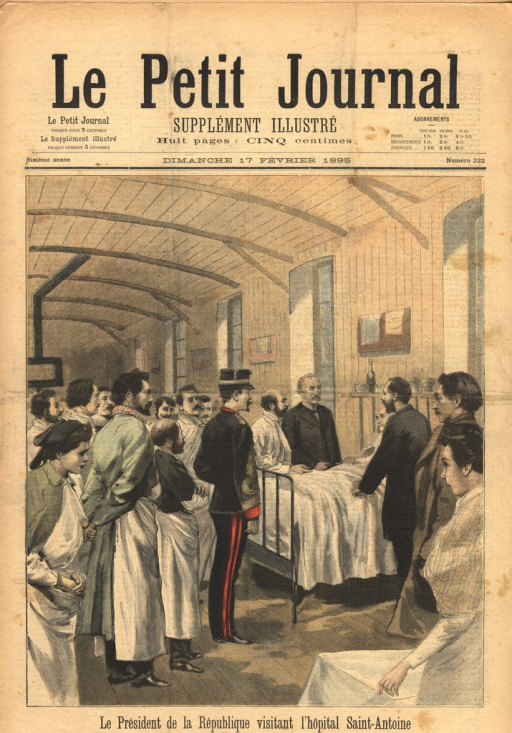 <p>The president stands in full regalia at the foot of a hospital bed in a ward.  A old patient sits in the bed and faces the president and the other officials and staff members who surround the bed.</p>