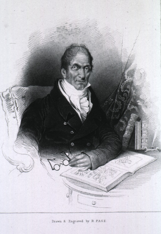 <p>Seated, arm on books, holding glasses.</p>