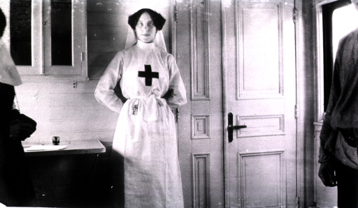 <p>A nurse stands against the wall of a hospital railroad car used as a surgical dressing room.</p>