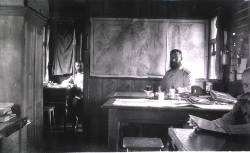 <p>Three soldiers(?) sit at desks at the advance medical supply depot office.</p>
