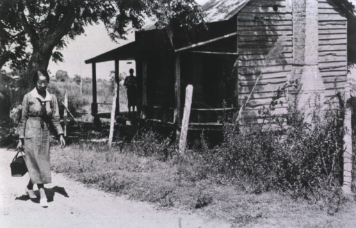 <p>An African American nurse walks past a wooden house; a woman (in silhouette) stands on the porch and watches the nurse.</p>