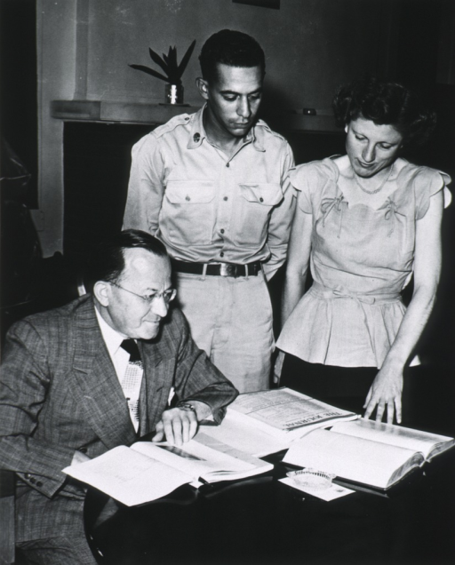 <p>Showing Dr. Goldstein seated at table, right pose; looking at several books.  Standing next to him are Pfc. Carillo and Myrline Triplett, librarian at William Beaumont General Hospital.</p>