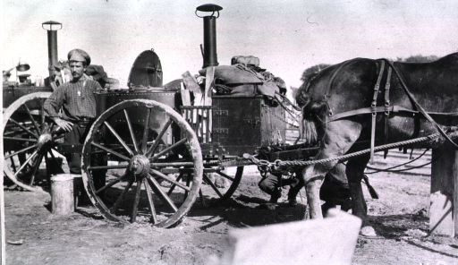 <p>A soldier(?) stands beside a field kitchen while two other soldiers(?) are bending down behind the horse and cart.</p>