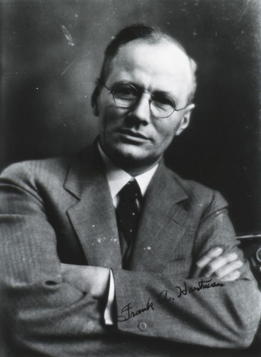 <p>Head and shoulders, full face; arms folded; wearing glasses.</p>