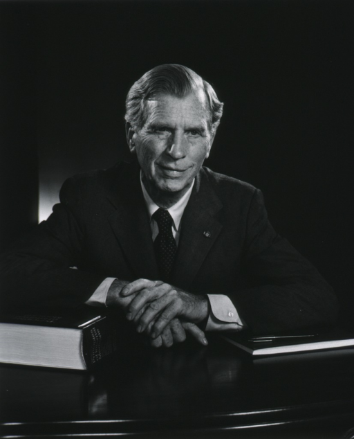 <p>Head and shoulders, full face, seated at a desk, with his hands clasped in front of him.</p>