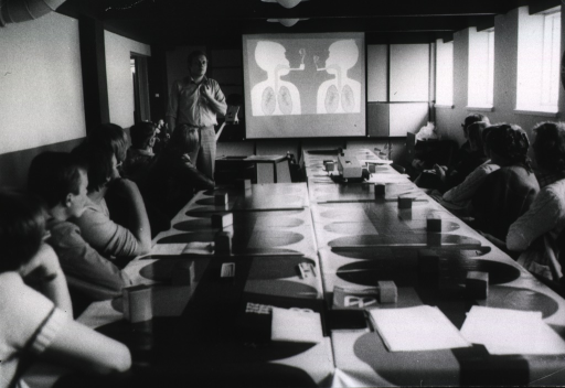 <p>Interior view of a seminar room: a man is lecturing, with the aid of slides, on the effects of smoking on the lungs.</p>