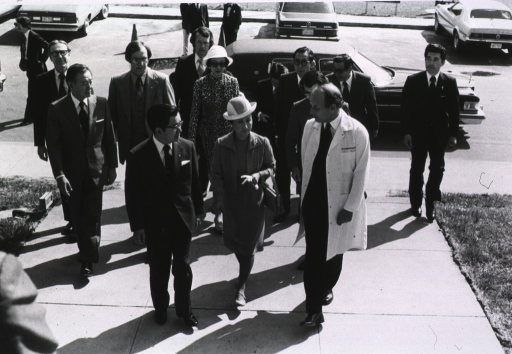 <p>Prince Masahito Hitachi, Princess Hanako Hitachi, and Dr. Donald S. Fredrickson, director of the National Institutes of Health, are outside together.  An entourage is following them.  There are parked cars behind them.</p>