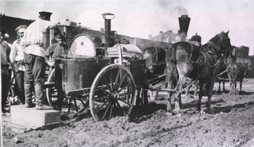 <p>A soldier serves others from the best sanitary cart kitchen pulled by horses.  Train cars are in the background</p>