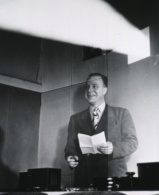 <p>Half-length, standing in projection room, left pose, full face; holding papers.</p>
