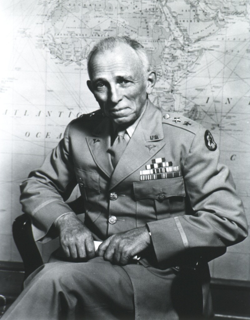 <p>Three-quarter length, seated, full face; wearing uniform; holding scroll; large wall map in background.</p>