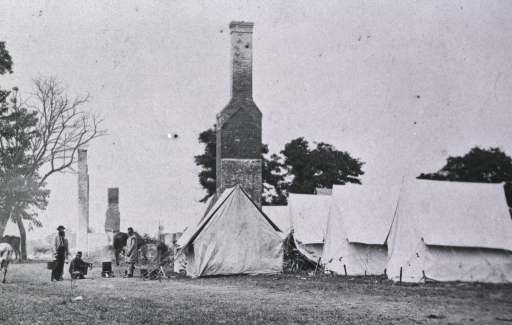 <p>Three soldiers are near tents pitched at the ruins of the White House.</p>