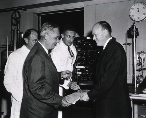 <p>Dr. James Watt and Dr. Samuel Fox explain to Congressman Laird how the application of biophysical and mathematical principles to the measurement of human circulatory functions provide valuable information on the &quot;horsepower&quot; of the human heart.</p>