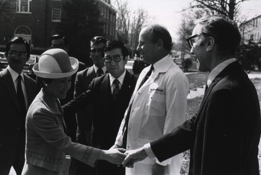 <p>The royal princess of Japan, Hanako Hitachi, is shaking hands with Dr. Arthur Upton, director of the National Cancer Institute (NCI).  Dr. Donald S. Fredrickson, director of the National Institutes of Health (NIH) is in a lab coat.  There are four men to Dr. Fredrickson's right.  In the background is police officer, a parking lot, two NIH buildings, and leaf-barren trees.</p>