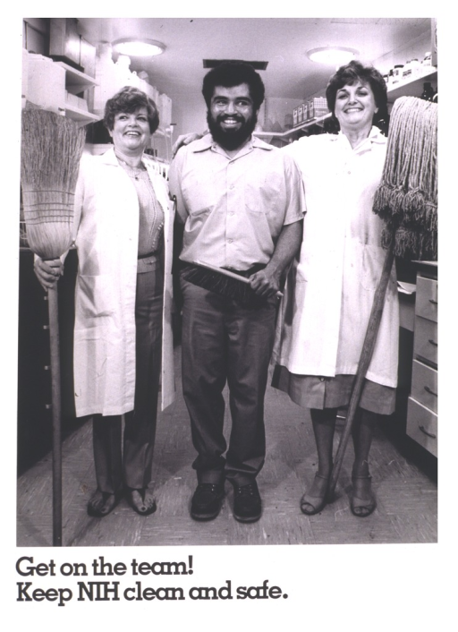 <p>A photograph of three smiling people with their arms around each other.  A white woman in a lab coat holds a broom, a black man in a uniform holds a brush, and another white woman in a lab coat holds a mop.</p>