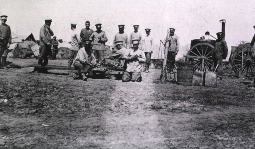 <p>Several soldiers are standing while others are sitting as they eat near a field kitchen.</p>